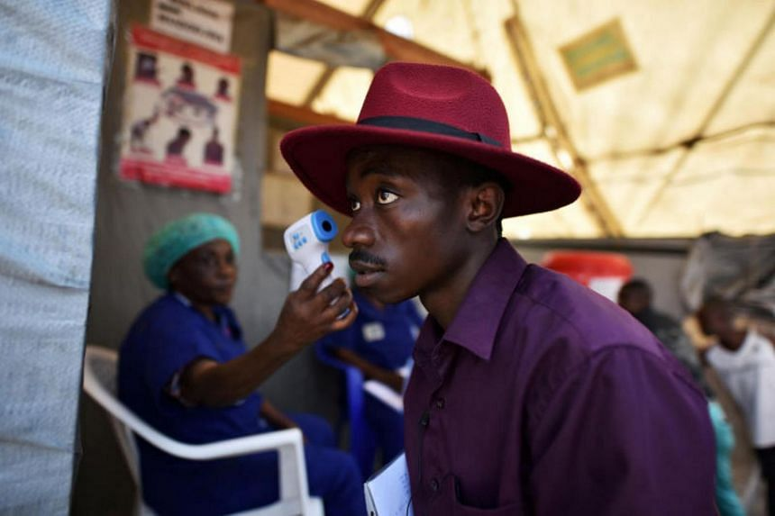 A health worker checks the temperature of a man as part of the Ebola screening upon entering the General Hospital in Goma on July 15, 2019.