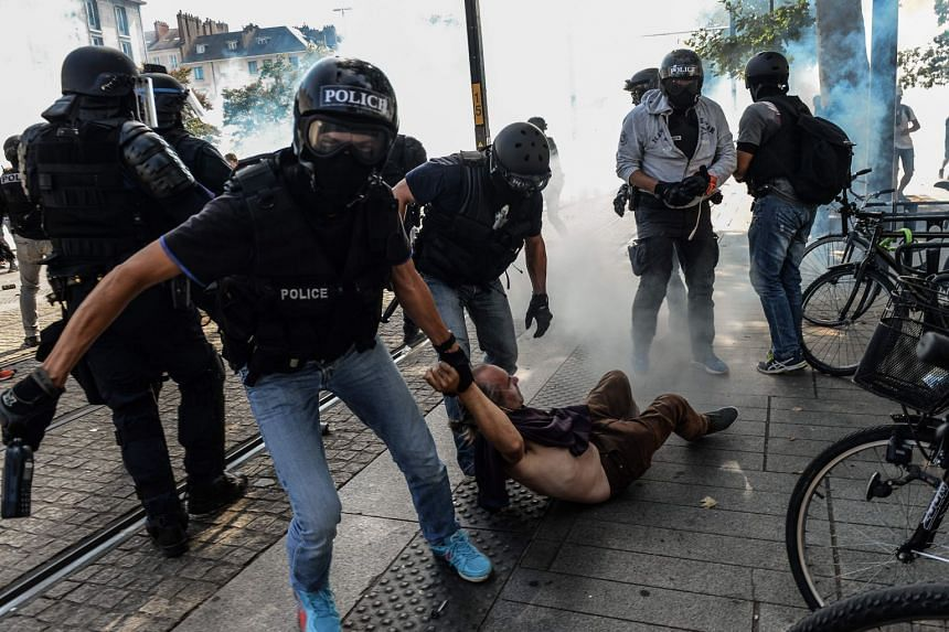 Anti-criminality brigade, or BAC, police officers arrest a man during a gathering in Nantes.