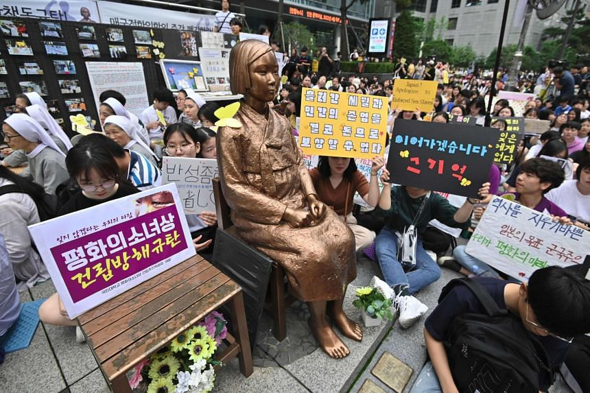 """South Korean protesters sit near a statue of a teenage girl symbolising """"comfort women"""" during a weekly anti-Japanese demonstration near the Japanese embassy in Seoul on July 24, 2019."""