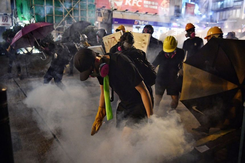 Disoriented protesters caught off guard and beating a hasty retreat after police fired tear gas outside Tsim Sha Tsui Police Station near Nathan Road last night. Police fired tear gas and pepper spray to disperse the crowd on the streets of Mongkok a