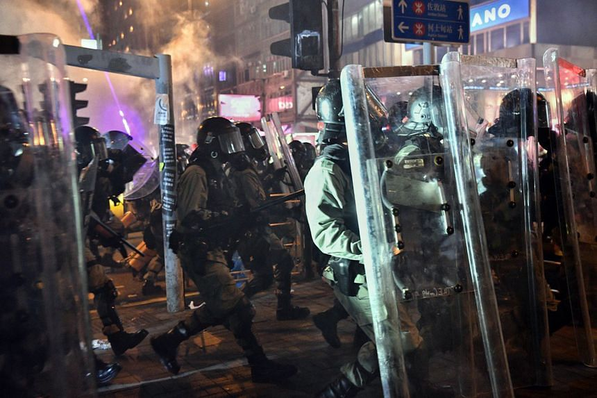 Police officers charging in towards the protesters after firing tear gas outside Tsim Sha Tsui station last night.