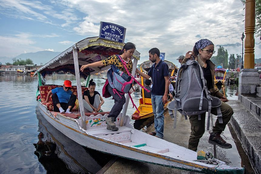 Tourists disembarking on the banks of Dal Lake as they prepare to leave Srinagar, in Indian-controlled Kashmir, yesterday. A security advisory about possible militant attacks caused panic and led to the departure of thousands of tourists, pilgrims an