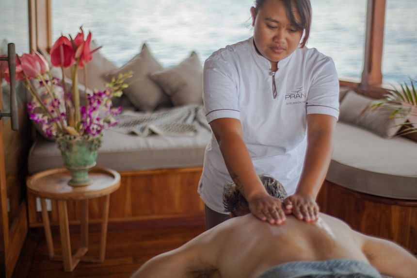 Get a massage (above) aboard the Prana by Atzaro, a high-end phinisi liveaboard hand-built in ironwood and teak that sleeps 18 in nine sumptuous en-suite cabins.