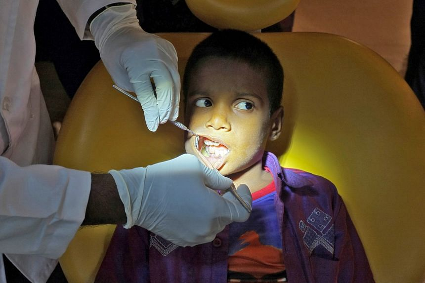 Unerupted teeth embedded in a tumor lodged in the jaw of a seven-year-old boy (above) being extracted in a hospital in Chennai, India.