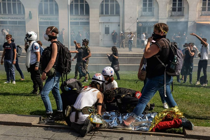 Street medics give assistance to a person during clashes on the sidelines of a gathering in Nantes.