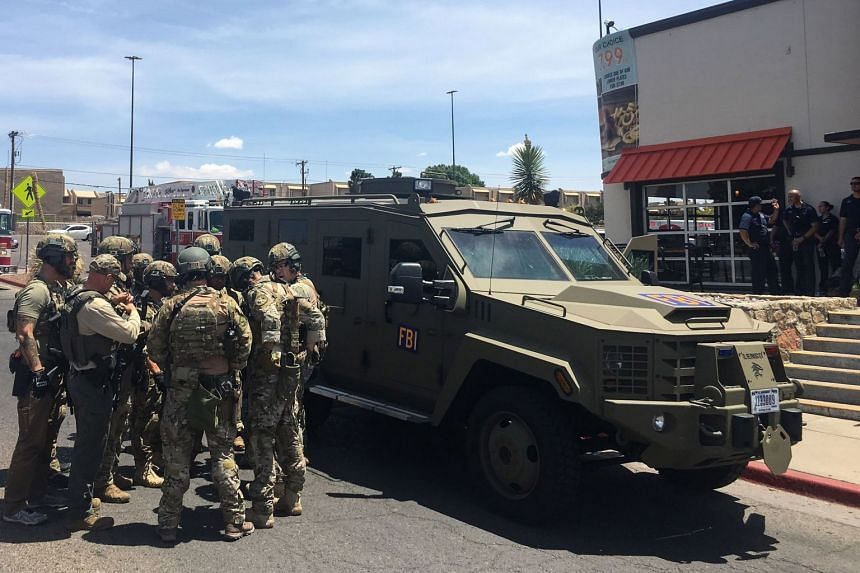 Armed police gather next to an FBI armoured vehicle near to the Cielo Vista Mall during the incident.