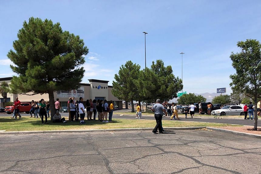 People stand outside the Cielo Vista Mall as an active shooter situation unfolds.