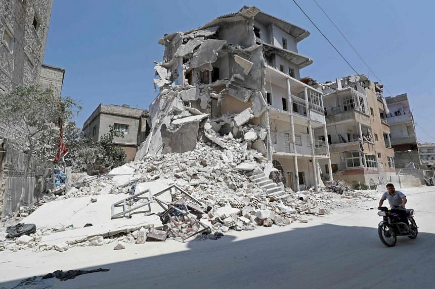 A Syrian man drives a motorcycle past destroyed buildings in the town of Ariha, in the south of Syria's Idlib province, on Aug 2, 2019.
