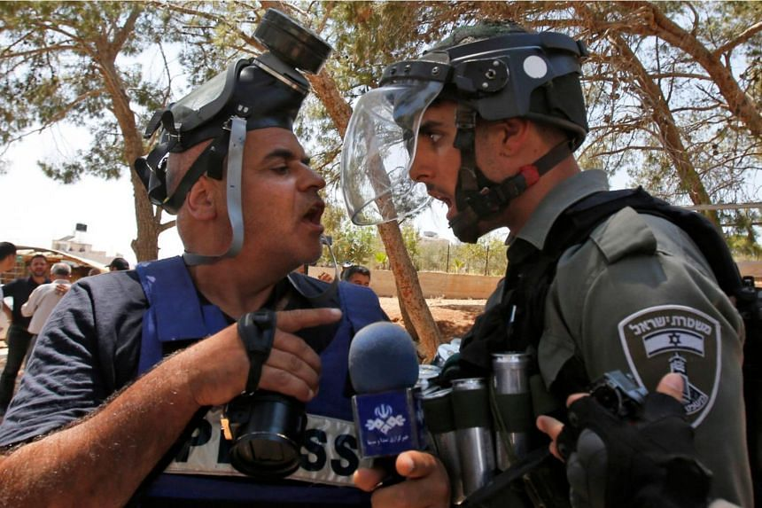 An Israeli border police confronting a journalist following clashes after the Friday prayers at the site of demolished buildings in the West Bank, adjacent to the area of Sur Baher in East Jerusalem, on Aug 2, 2019.