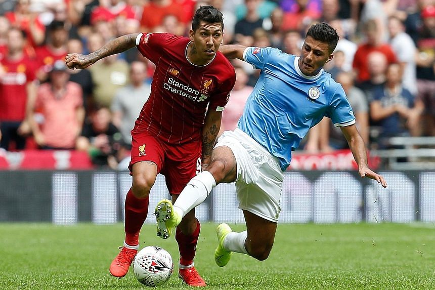 Liverpool's Roberto Firmino (left) and Manchester City's Rodrigo tussling for the ball at yesterday's Community Shield match. PHOTO: AGENCE FRANCE-PRESSE