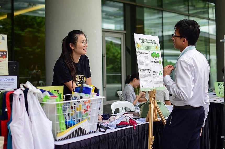 A booth at an NUS Save event with a poster about the textiles recycling programme. An online survey of 4,097 Singapore respondents by research agency YouGov in 2017 found that 73 per cent had thrown away clothes in the past year while 34 per cent had