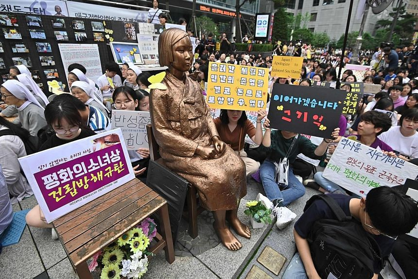 """Protesters surrounding a """"comfort women"""" statue near the Japanese embassy in Seoul last month. Activists have set up dozens of statues in honour of victims who were sex slaves for Japanese soldiers in World War II, but the statues have drawn Tokyo's"""