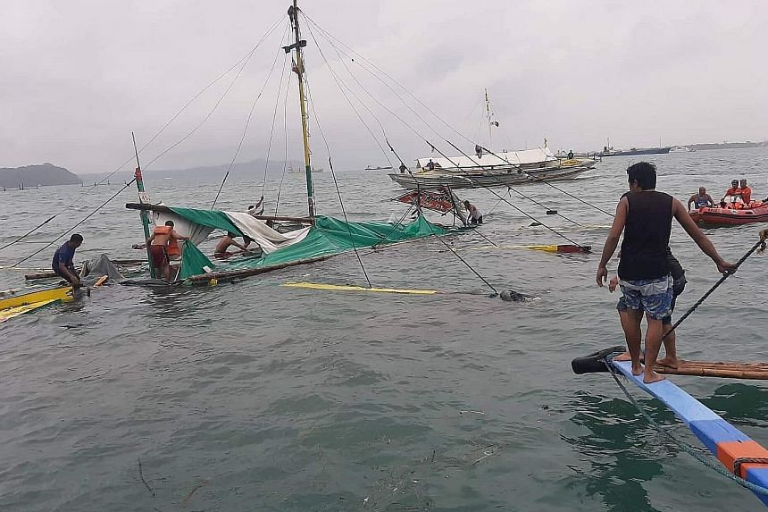 One of the outrigger boats, partially submerged, in the waters off Iloilo city in the Philippines last Saturday. Twenty bodies were recovered in rough seas yesterday, adding to the 11 retrieved earlier.