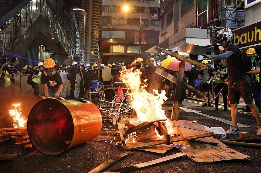 Protesters flashing laser beams as riot police volleyed multiple rounds of tear gas to disperse the crowd during yesterday's protest. PHOTO: ASSOCIATED PRESS In a bid to slow the police's advance at Causeway Bay, a group torched rubbish bins and wood