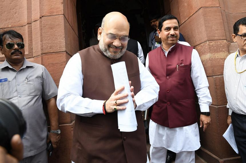 Home Minister Amit Shah (in brown) urged members of parliament to discuss the legislation that seeks to end autonomous status for Muslim-majority Kashmir, which allows only residents to buy property and hold state government jobs.