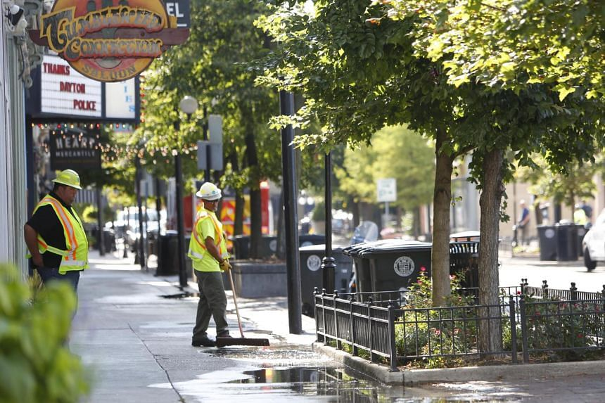 Workers clean the pavement after a shooting in the Oregon District of Dayton, Ohio, on Aug 4, 2019.