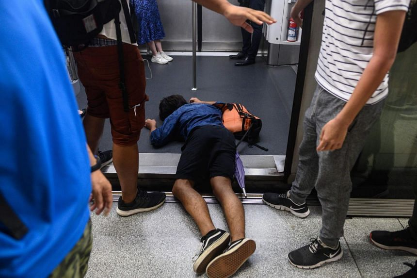A man falls during a protest to prevent commuters from reaching work in business districts at Lai King MTR station in Hong Kong, on Aug 5, 2019.