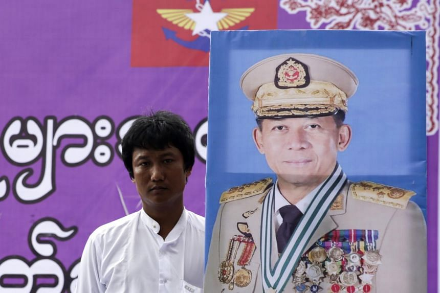 A man holds a portrait of military commander-in-chief Senior General Min Aung Hlaing during a rally to denounce the US sanctions imposed on senior Myanmar military officials, in Yangon, Myanmar, on Aug 3, 2019.
