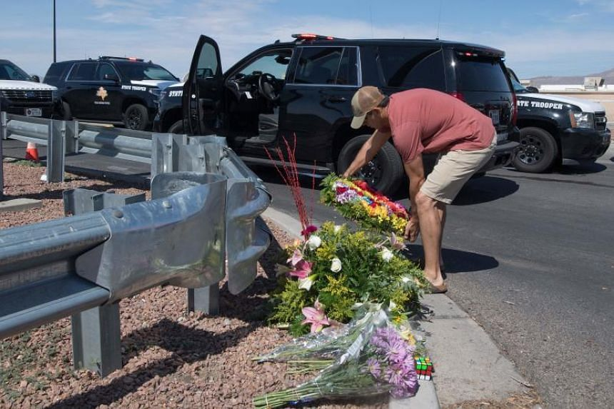 A man places flowers at a makeshift memorial outside the Cielo Vista Mall Walmart where a shooting left 20 people dead in El Paso, Texas, on Aug 4, 2019.