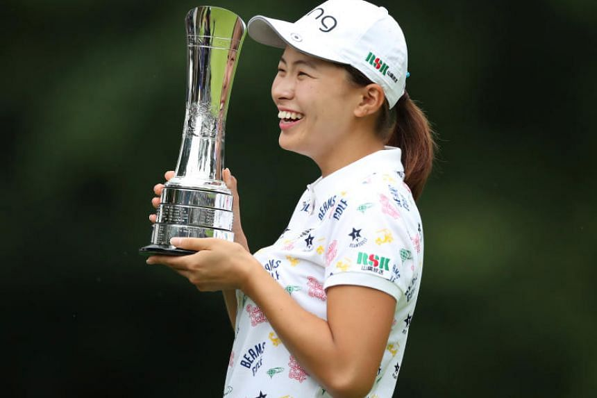 Japan's Hinako Shibuno celebrates with trophy after making a birdie putt on the 18th hole to win the Women's British Open.