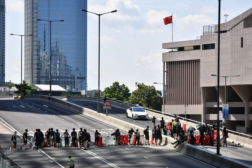 Protesters set up a roadblock on Hardcourt Road in front of the People's Liberation Army Hong Kong Building on Aug 5, 2019.