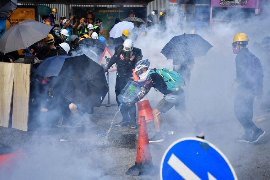 Protesters dousing tear gas canisters fired by police during clashes outside the Legislative Council complex in Hong Kong on Aug 5, 2019.