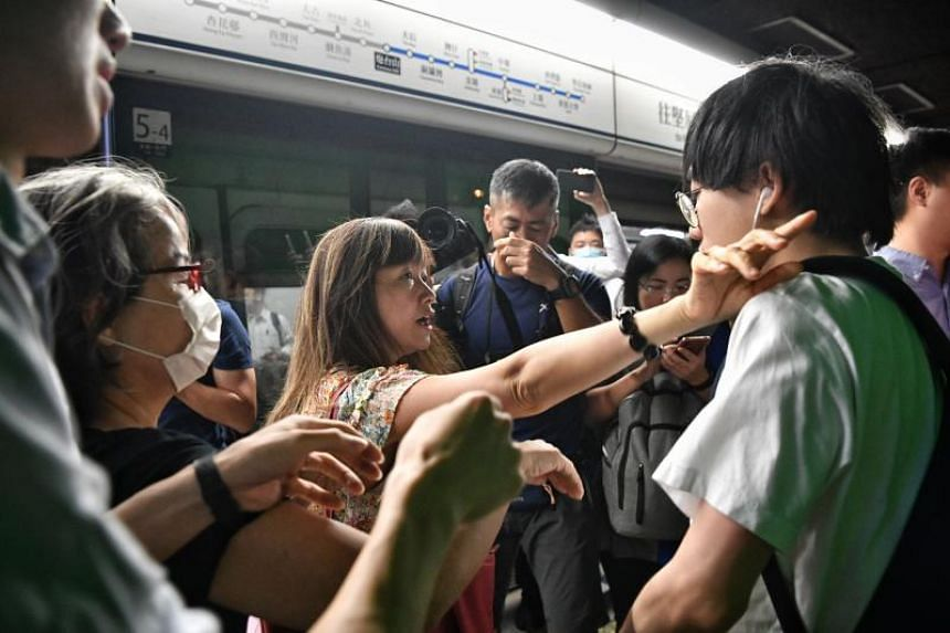 Protesters clash with passenges during a train disruption at Fortress Hill MTR station in Hong Kong on Aug 5, 2019.