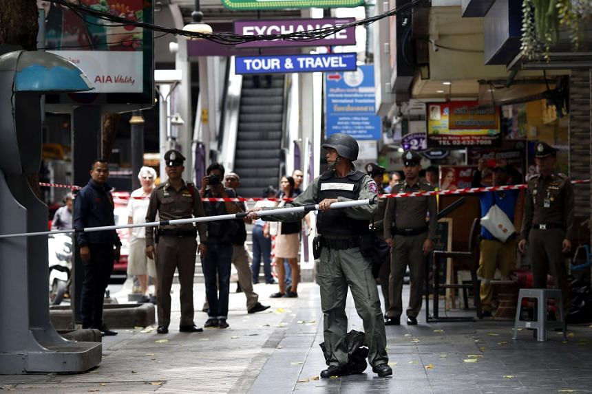 A member of the Explosive Ordnance Disposal unit inspects a suspicious object on Silom Road in Bangkok on Aug 2, 2019. Six bombs exploded in the Thai capital last Friday, and the authorities now say six other fire-bombs also went off that day.