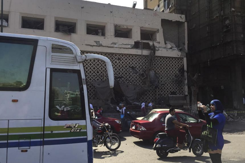 People survey the aftermath of a fiery car crash outside the National Cancer Institute in Cairo, Egypt, on Aug 5, 2019. The hospital had to be partially evacuated and there was apparent damage up to the building's third floor.