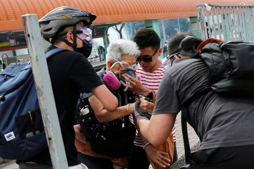 Demonstrators help an elderly woman after police fired tear gas during a demonstration at Tin Shui Wai on Aug 5, 2019.