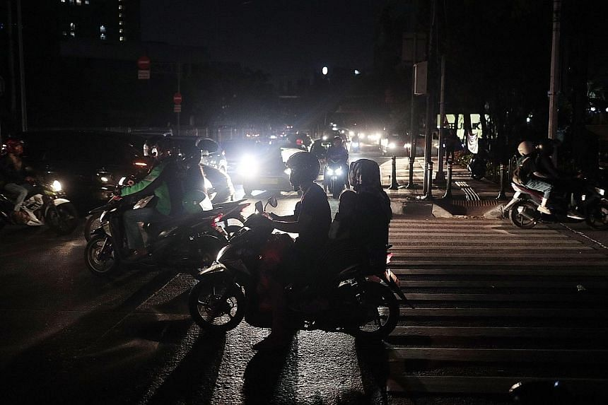 Motorists in Jakarta navigating darkened streets during the massive power outage on Sunday. PHOTO: ASSOCIATED PRESS