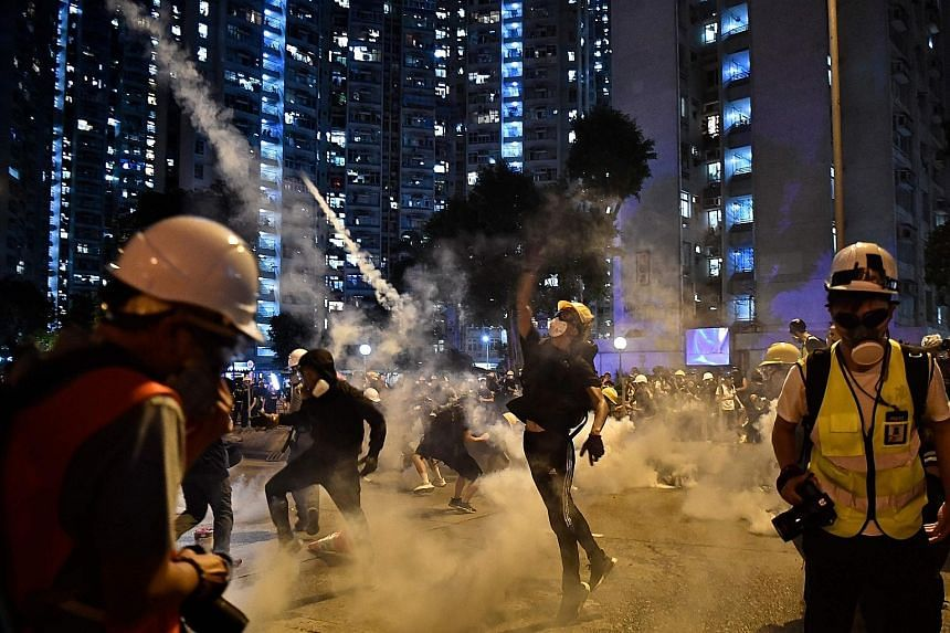 Protesters throwing tear gas canisters back at the police in Wong Tai Sin, in Kowloon, yesterday. Riot police spent most of the day battling anti-extradition protesters who had either surrounded police stations or built barricades on the roads in at