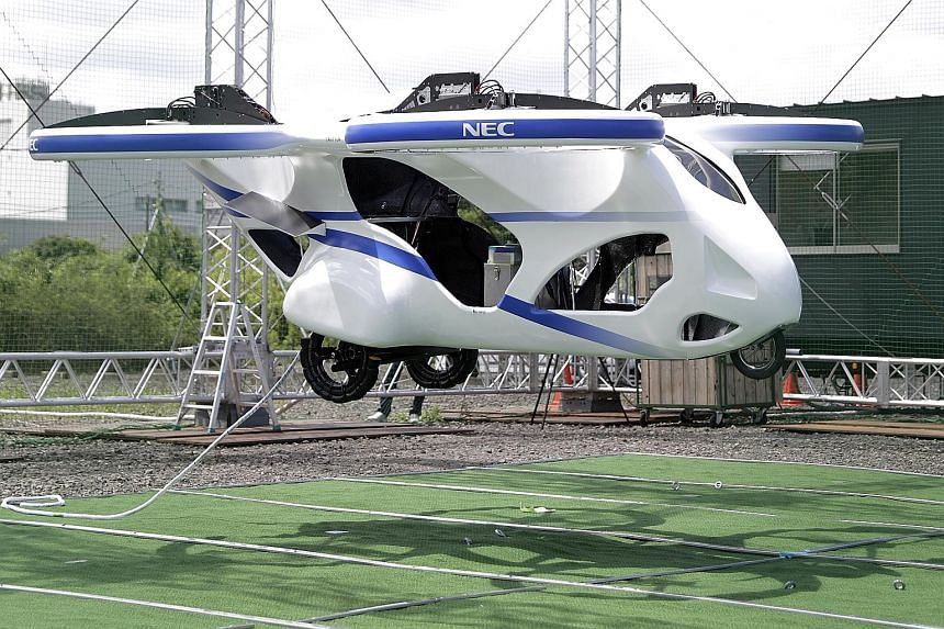 A prototype of NEC Corp's flying car hovering in the air during a demonstration at a testing site of the company's plant in the Japanese city of Abiko in Chiba prefecture. The flying vehicle is essentially a large drone, with four propellers, that is