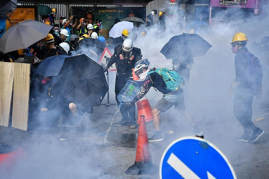 Above: Demonstrators gathering to block the Cross Harbour Tunnel in Hong Kong's Hung Hom district yesterday. Key roads were blocked, cutting major arteries linking Hong Kong Island and the Kowloon peninsula. PHOTO: BLOOMBERG Right: Protesters rushing