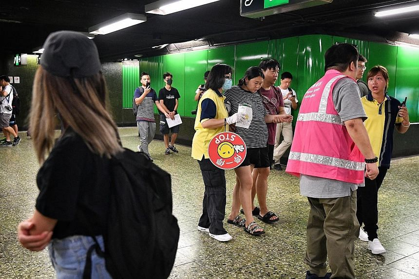 A pregnant commuter being helped by her husband and MTR staff at Fortress Hill MTR station after protesters disrupted rail services yesterday morning. ST PHOTO: CHONG JUN LIANG