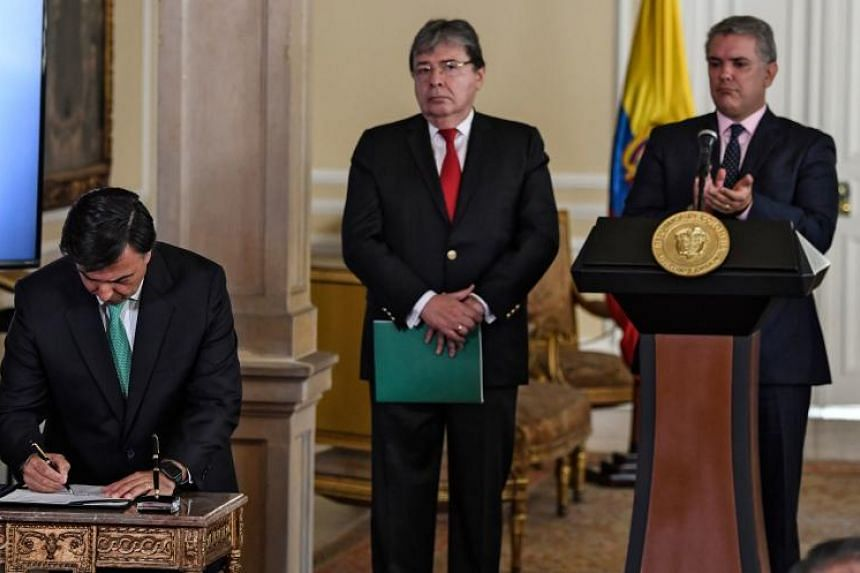 The head of the Colombian National Registration Office of Civil Status Juan Carlos Galindo (left) signs a decree that allows the nationalisation of 24,000 children of Venezuelan parents born in Colombia next to Colombian Foreign Minister Carlos Holme