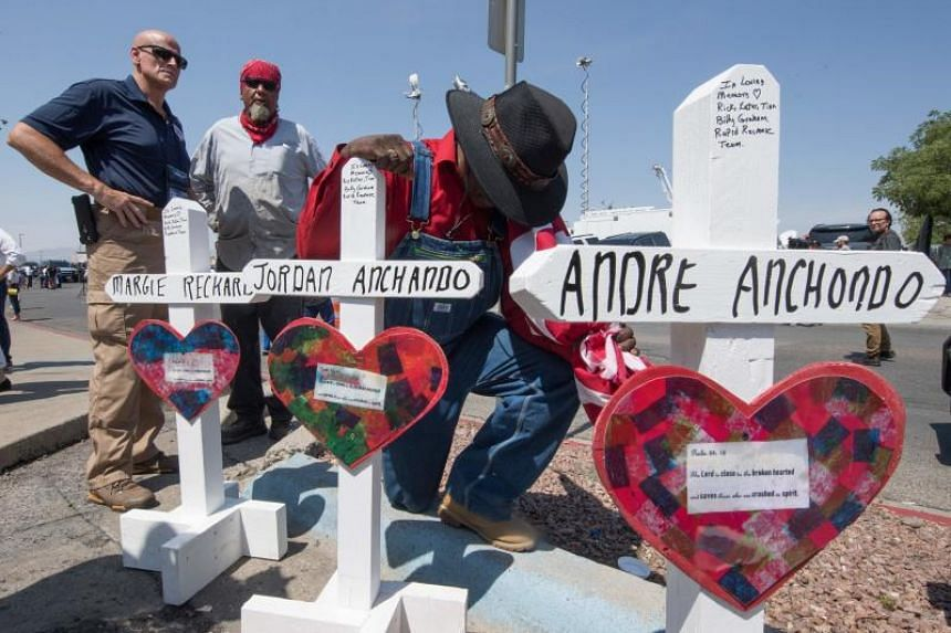 A man prays beside crosses with the names of victims who died at a makeshift memorial after the shooting that left 22 people dead at the Cielo Vista Mall WalMart in El Paso, Texas, on Aug 5, 2019.