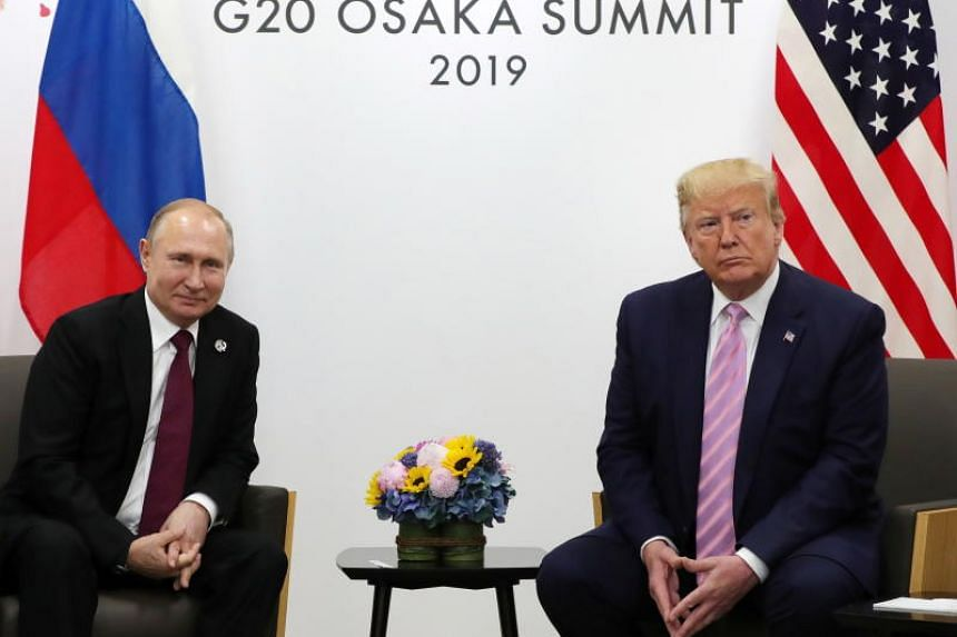 In this file photo from June, Russian President Vladimir Putin (left) and US President Donald Trump meet on the sidelines of the G20 summit in Osaka. Putin ordered the defence and foreign ministries and Russia's SVR foreign intelligence service to cl