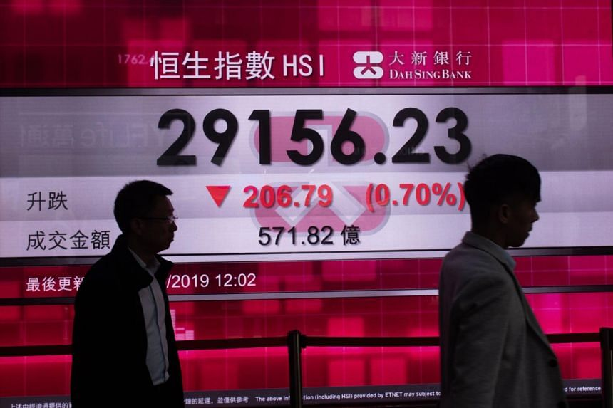 In a file photo taken on May 8, pedestrians walk in front of a stock display board that shows the Hang Seng Index.