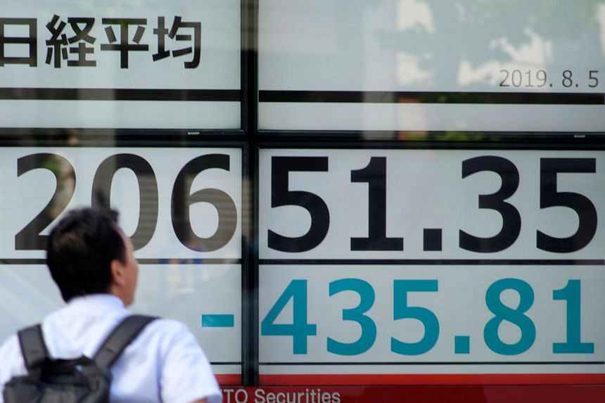 In this file picture taken on Aug 5, a man walks in front of an electronic stock indicator displaying the share price of the Tokyo Stock Exchange in Tokyo.