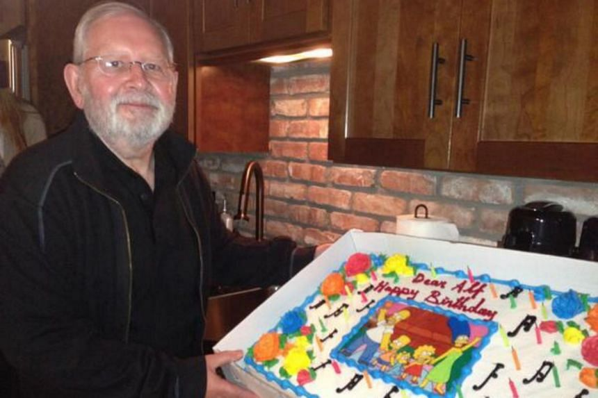 Veteran composer Alf Clausen poses with a Simpsons cake in a photo taken in 2014.
