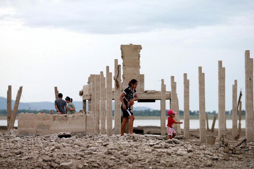 In this file picture taken on Aug 1, people walk through the ruins of a Buddhist temple, which has resurfaced in a dried-up dam due to drought, in Lopburi, Thailand.