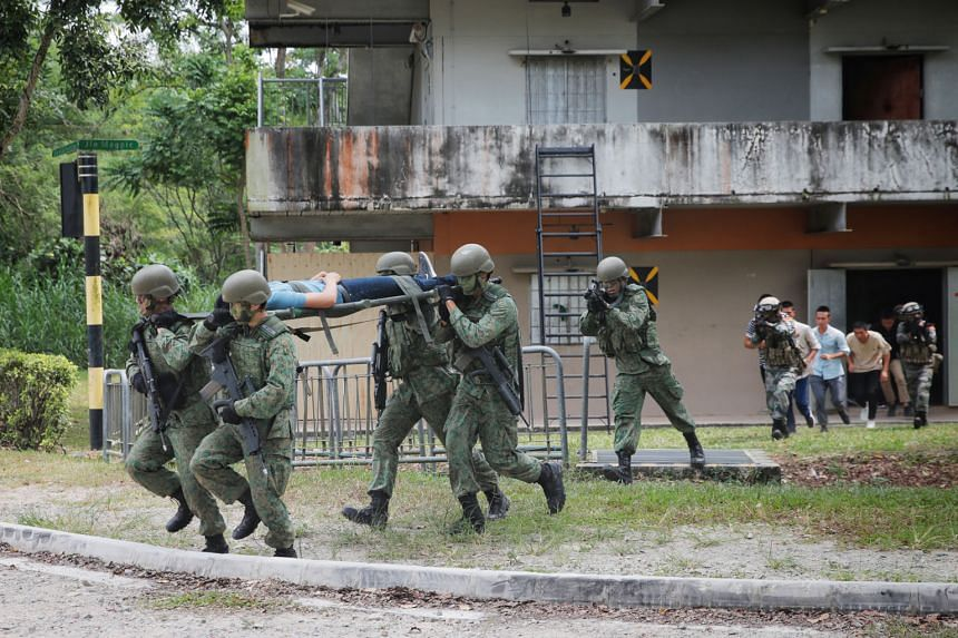 """Troops from Singapore and China evacuating """"civilians"""" from the Murai Urban Training Facility yesterday. The raid marked the culmination of this year's 10-day Exercise Cooperation, in which about 120 soldiers from each side took part."""