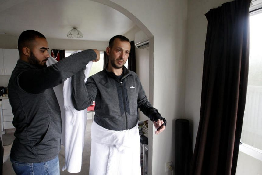 Mr Temel Atacocugu (right), who was shot nine times during the Christchurch mosque attacks, tries on the clothes he will wear during the Haj pilgrimage, in Christchurch, New Zealand.