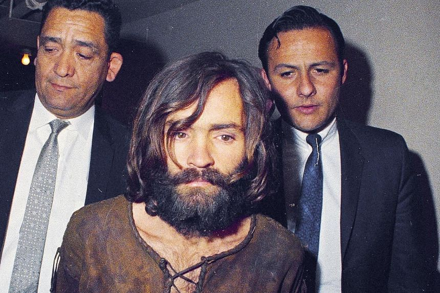 Charles Manson (far left, foreground, in a 1969 file photo) being escorted to his arraignment on conspiracy-murder charges. Manson (left, in a 2017 file photo) died in prison on Nov 19, 2017.