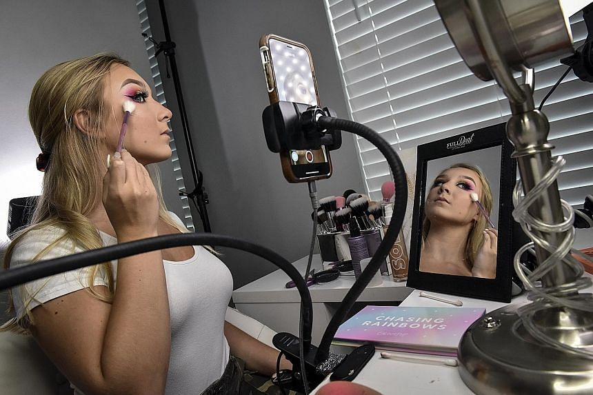 Sydney Sikes, 15, in her bedroom applying make-up for her Instagram feed.