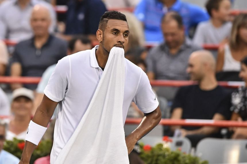 Kyrgios holds his towel in his mouth during his match against Kyle Edmund of Great Britain.