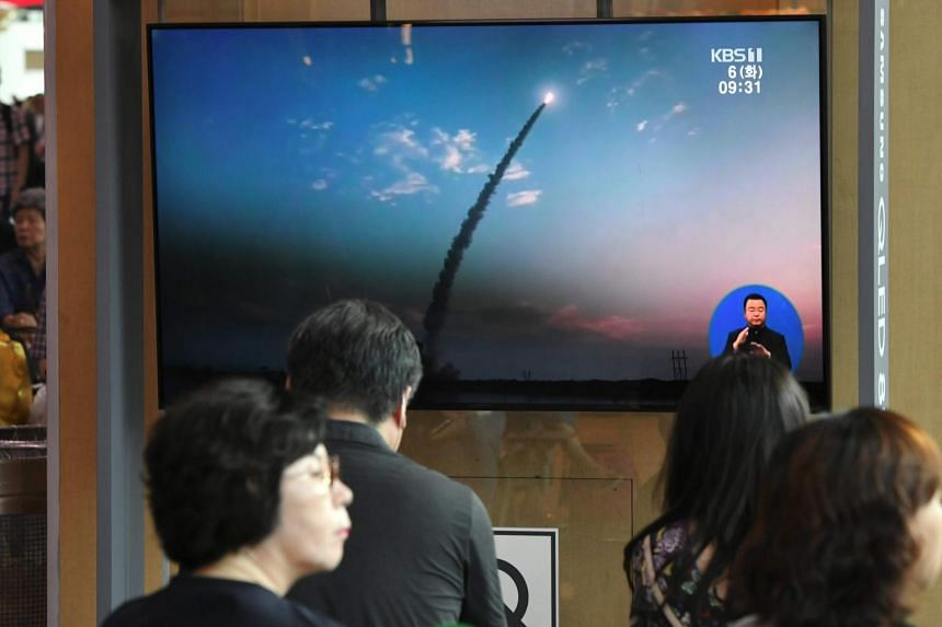 """In this picture taken on Aug 6, 2019, people watch footage of North Korea's missile launch. US prosecutors suspect that a state-owned North Korean bank used a Chinese front company to export """"hundreds of millions of dollars"""" in coal and other mineral"""