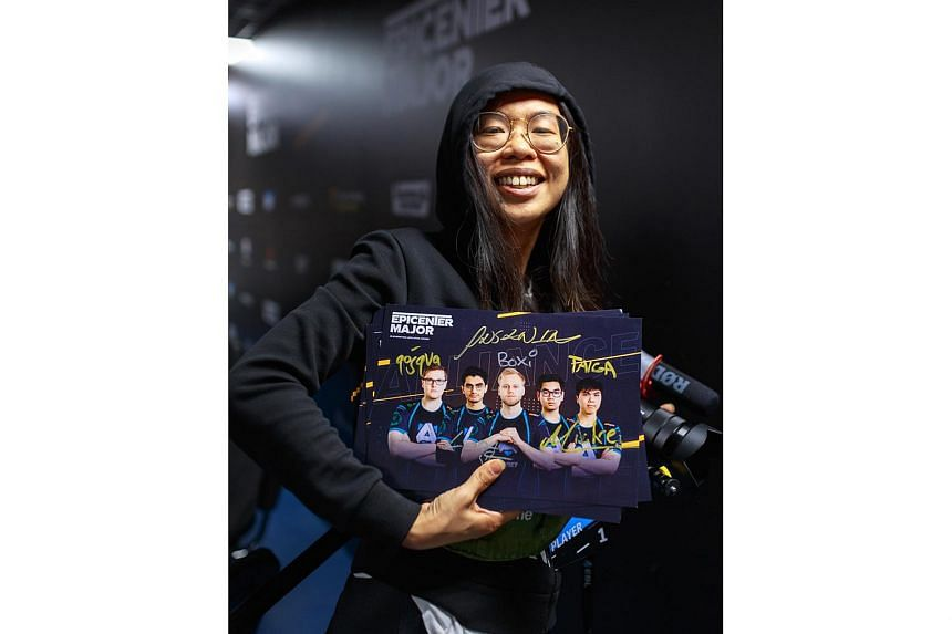 Ms Kelly Ong (above) at the Dota 2 Epicenter Major tournament in Moscow in June, with autographed posters of Alliance's current five-man Dota 2 roster. She officially became a co-owner of Alliance last December and wants to eventually return to Sin