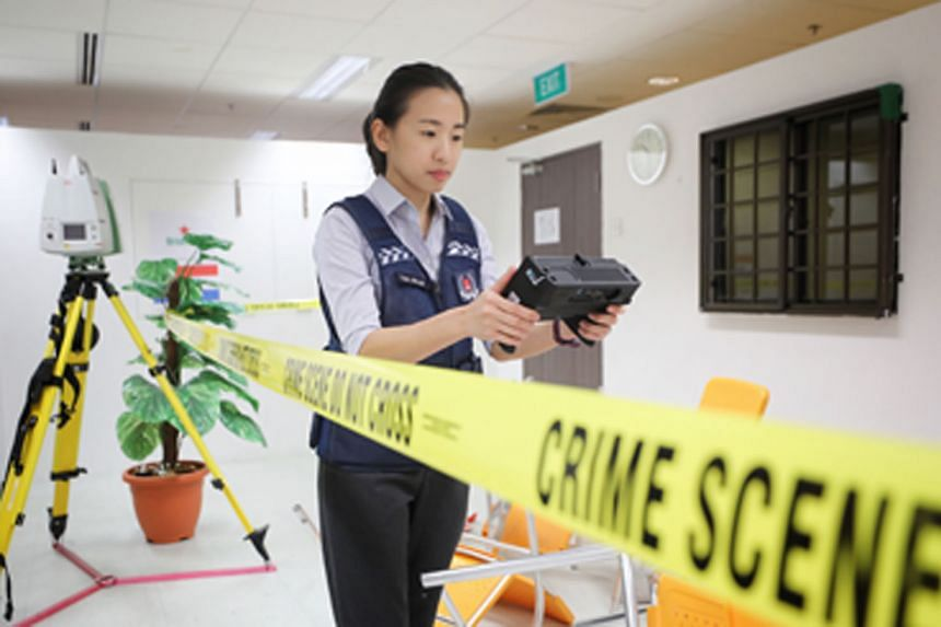 Ms Tan Joe-Lin, who supervises a team of crime scene specialists, using a handheld 3D scanner that is used to document crime scenes. The scanner can examine hard-to-reach places and the user can immediately see what was scanned and redo it if need be